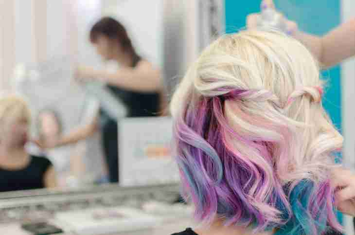 image of back of hair model with blonde hair with a mix of pink and purple faded pastel highlights