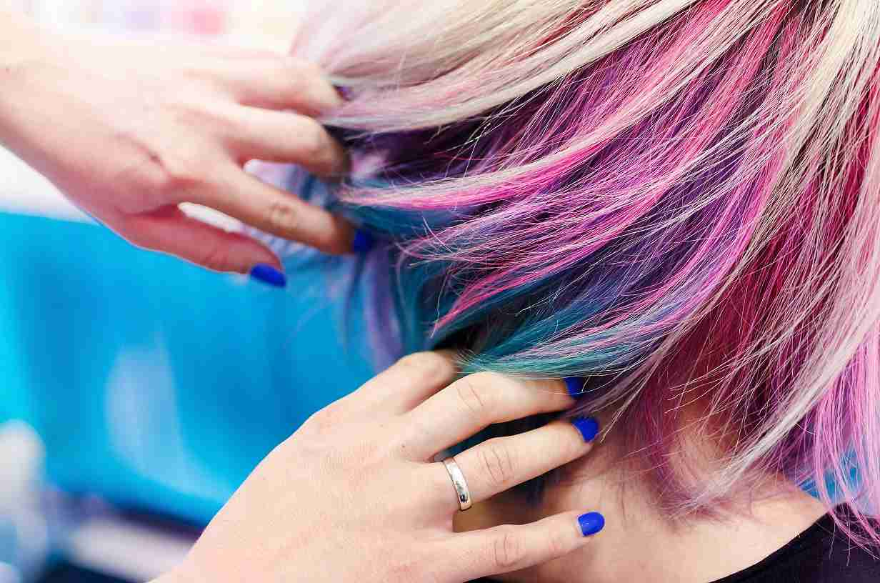 pink and blue hair being styled by someone who is training for a hairdressing career