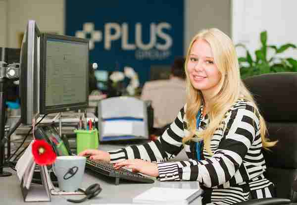smiling administration apprentice sitting at desk at Plus Group LIverpoolt